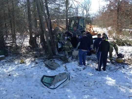 Rescue workers surround the white sedan where the driver