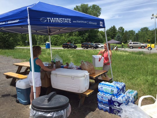 Dawn Juneau and Devi Momot stage a refreshment station for officers conducting a roadblock along New York State Route 374 in Morrrisonville Sunday.