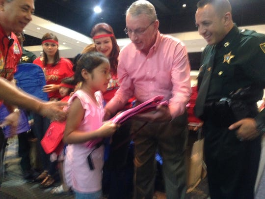 Lee Co. commissioner John Manning helps Kimberly Aguilar, 7, of Fort Myers. the first backpack recipient at the Big Backpack Event at Harborside Event Center.