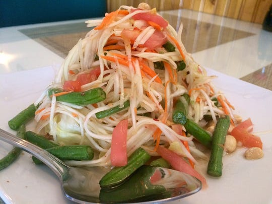 A green-papaya salad with tomatoes, peanuts and long beans in a dressing of lime, chilies and fish sauce.