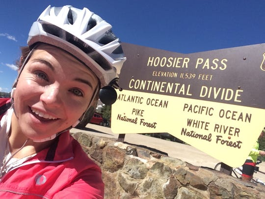 McKaylie Miller snaps a selfie with the sign for Hoosier Pass and the Continental Divide in the background earlier this summer as she and her father, Dana Miller made way across the United States on their tandem bicycle.