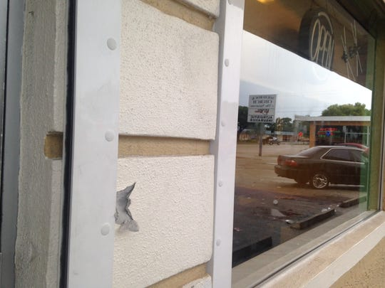 A mark from a bullet graces the front of a Creole-themed restaurant on Fowler Street, the scene of a fatal shooting early Monday.