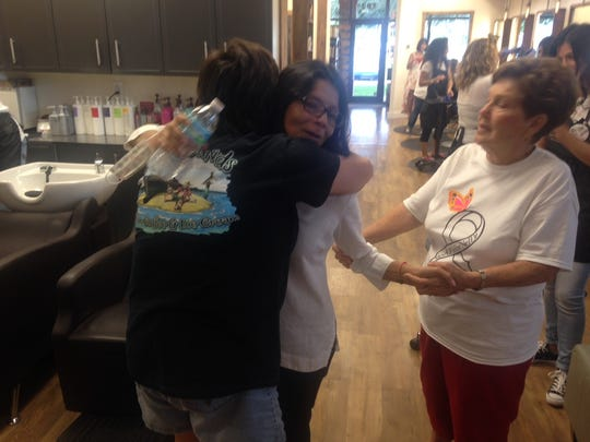 Nelly Truax receives a hug from a client at Cre8 Salon