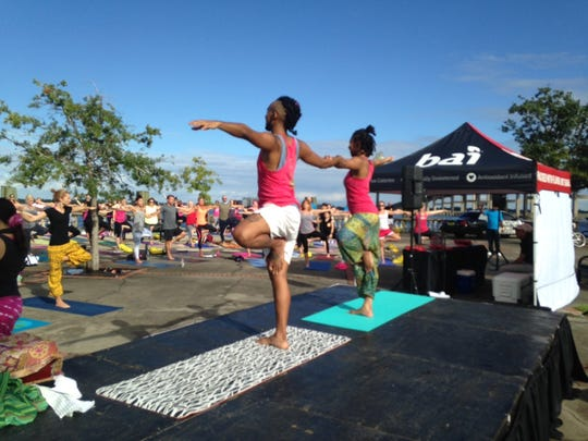Xyzo and Jasmine Johnson, both teachers in training at Florida Yoga Academy in Cape Coral, demonstrat yoga poses during the Yoga in the Steps event Sunday in Centennial Park.