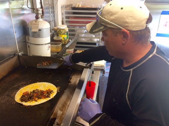 The Munch Mobile owner Chad Morgan layers his hand-cut steak onto a quesadilla for a customer at his south Fort Myers food truck.