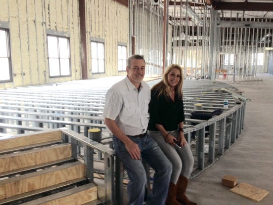 Tim and Julie Gilliland perch on the frame for the stage in the meeting area in the planned River Crossing Event Center where their Church out of Church intends to move.