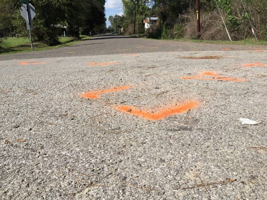 Orange spray paint marks the scene of a Tuesday night shooting in which a 6-year-old boy died. Four Marksville city marshals were chasing the boy's father, who was seriously wounded.