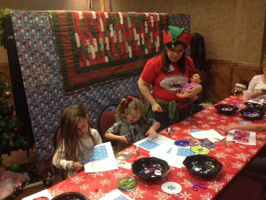 Elves were on duty all day to help young Jubilee visitors turn used CD's into Christmas ornaments.