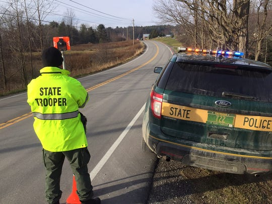 A Vermont State Police trooper stands on the side of