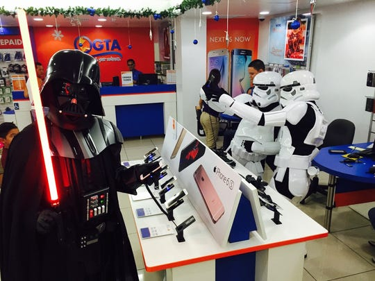 """Darth Vader shops for a smart phone at GTA while his Storm Troopers take a selfie during the opening night of """"Star Wars: Episode VII — The Force Awakens"""" at the Agana Shopping Center Dec. 17."""