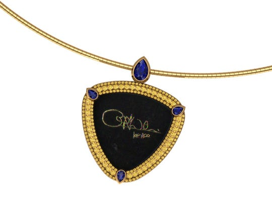 One of forty auction lots, this custom guitar pick necklace by Mark Loren will be auctioned off with a bass guitar from Cliff Williams.