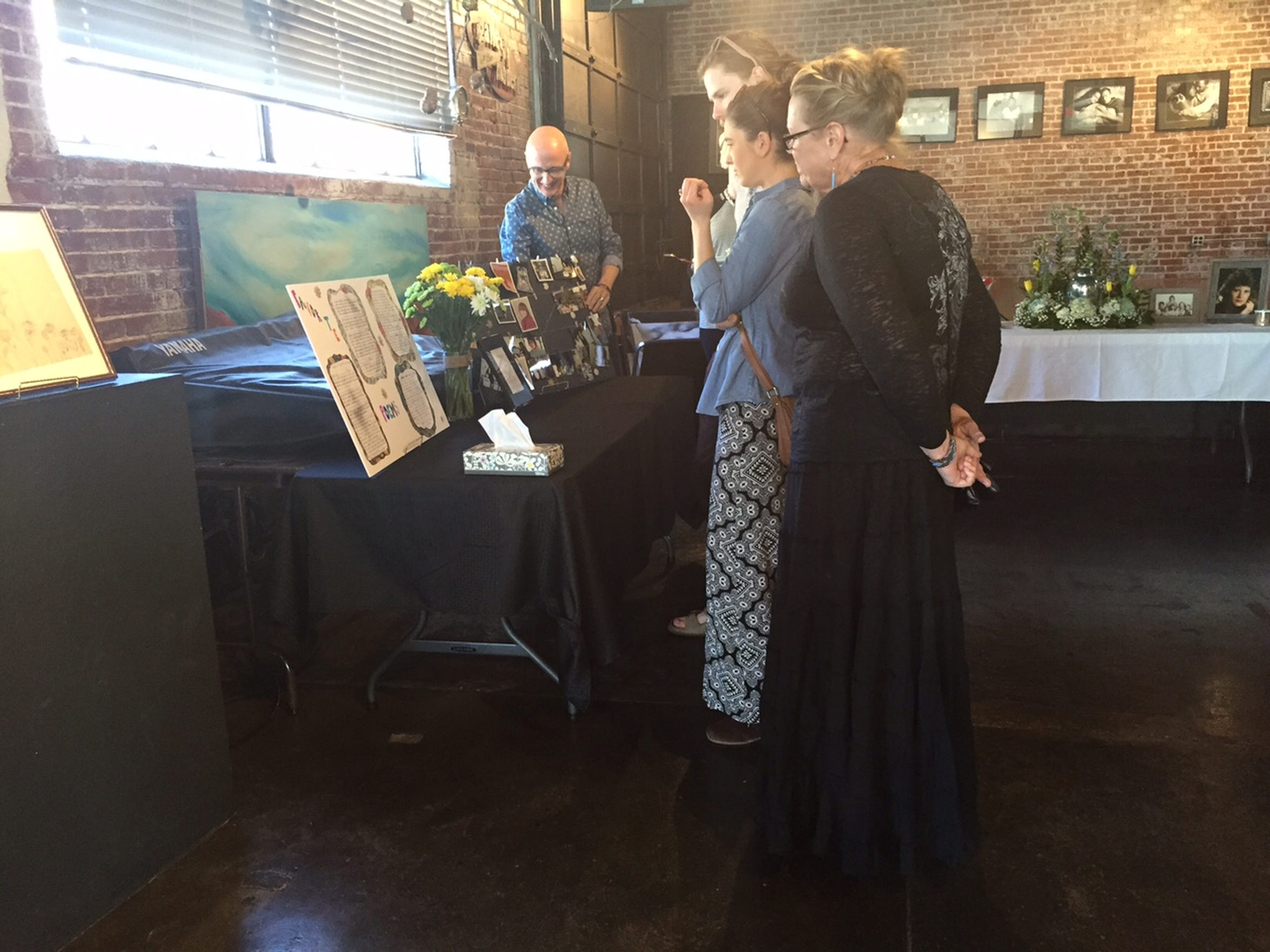 Friends and family look at Hensler's favorite poems and old photos at the memorial Saturday.