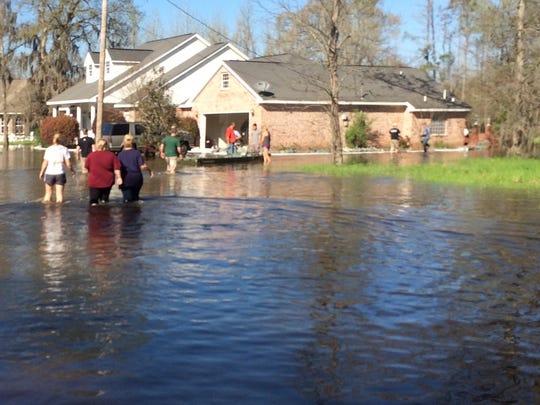 Volunteers help sandbag homes on Gingko Drive.