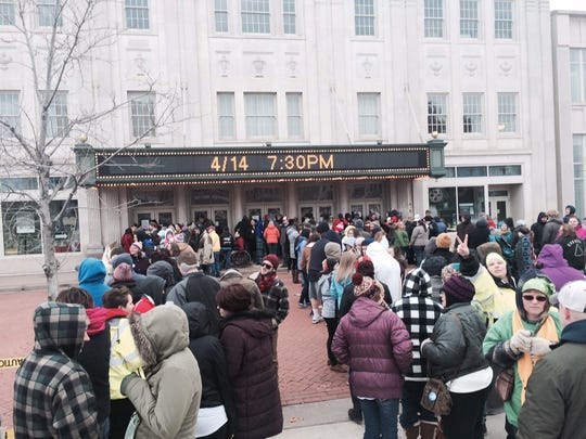 People gather in front of The Grand theater in downtown