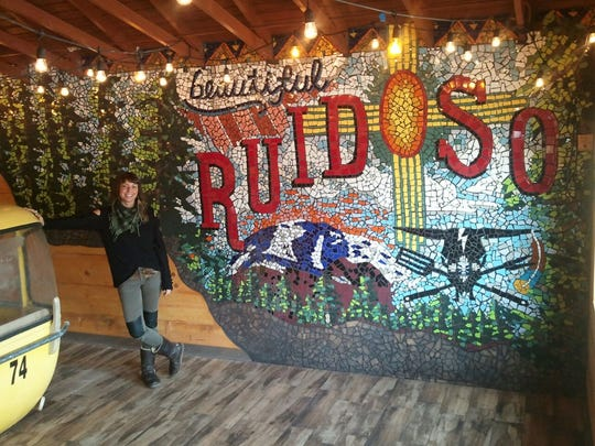 Summer Sarinova stands in front of her creation that graces the new dining room at Can't Stop Smokin' - the 130-foot mosaic-filled postcard featuring many the aspects of what's made our mountain town famous for decades.