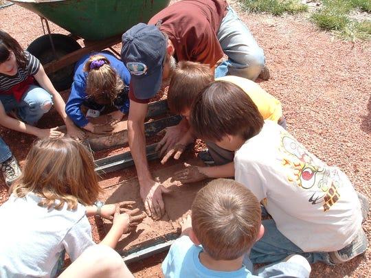 Children learn to make adobe bricks during the 2005 Earth Day Celebration in Springdale.