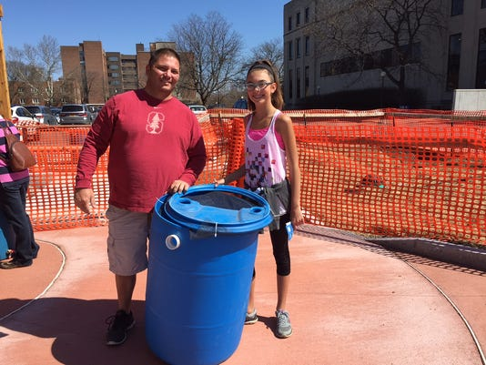 Father and daughter build a rain barrel.