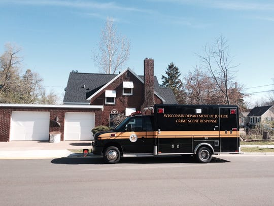 A state investigation vehicle is parked outside a home