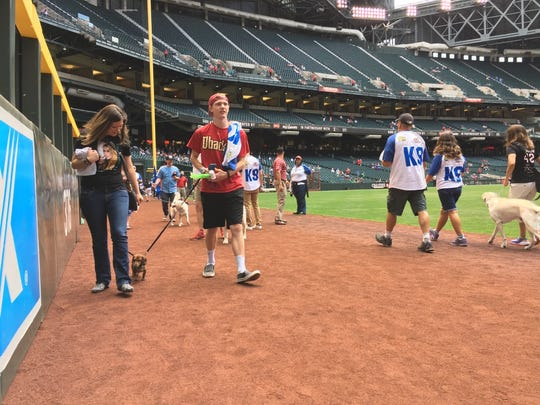 Sara and Sean Plaum of Phoenix walk with their dachshund, Joey, at Chase Field's Bark at the Park on Sunday.