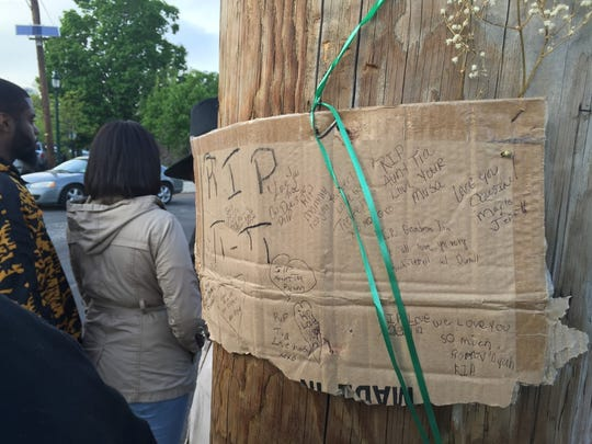 Memorial messages to Tia Walker cover a makeshift sign at a Camden memorial site.