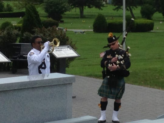 """York County Sheriff's Deputy Stephon Scott plays """"Taps"""" on the bugle at Prospect Hill Cemetery and Springettsbury Township Police Officer Jamie Miller plays """"Amazing Grace"""" on the bagpipes."""