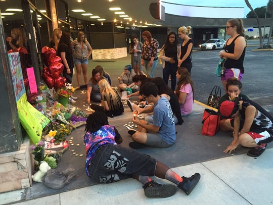 Fans hold an impromptu candlelight vigil Saturday for
