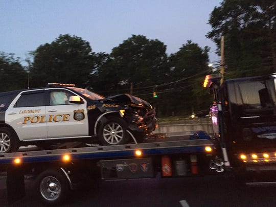 A Larchmont police cruiser is towed away from the crash scene on Saturday evening.