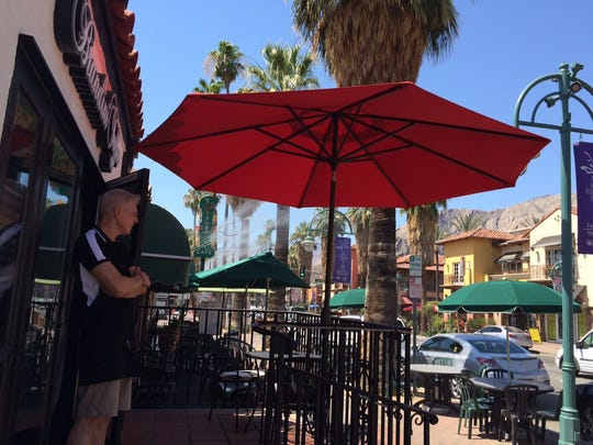 Steven Tifft, manager at Brandini Toffee in Palm Springs, stands under an umbrella that was in place to prevent heat from entering the front of the store.