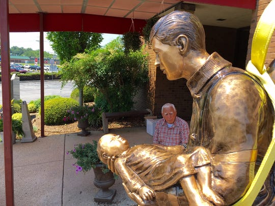 Joseph Vattilana checks out the $50,000 bronze statue he donated to the Talleyville Fire Company.