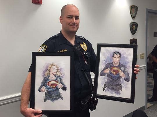 Morristown Police Sgt. Michael Molnar with renderings of Superman and Supergirl that the department will give out free at the Garden State Comic Fest July 9-10, 2016.