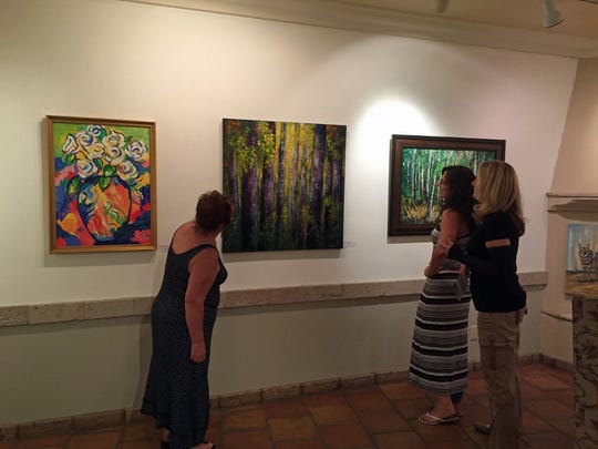 Visitors view art exhibited by the Sonoran Arts League at The Gallery at el Pedregal in Scottsdale.