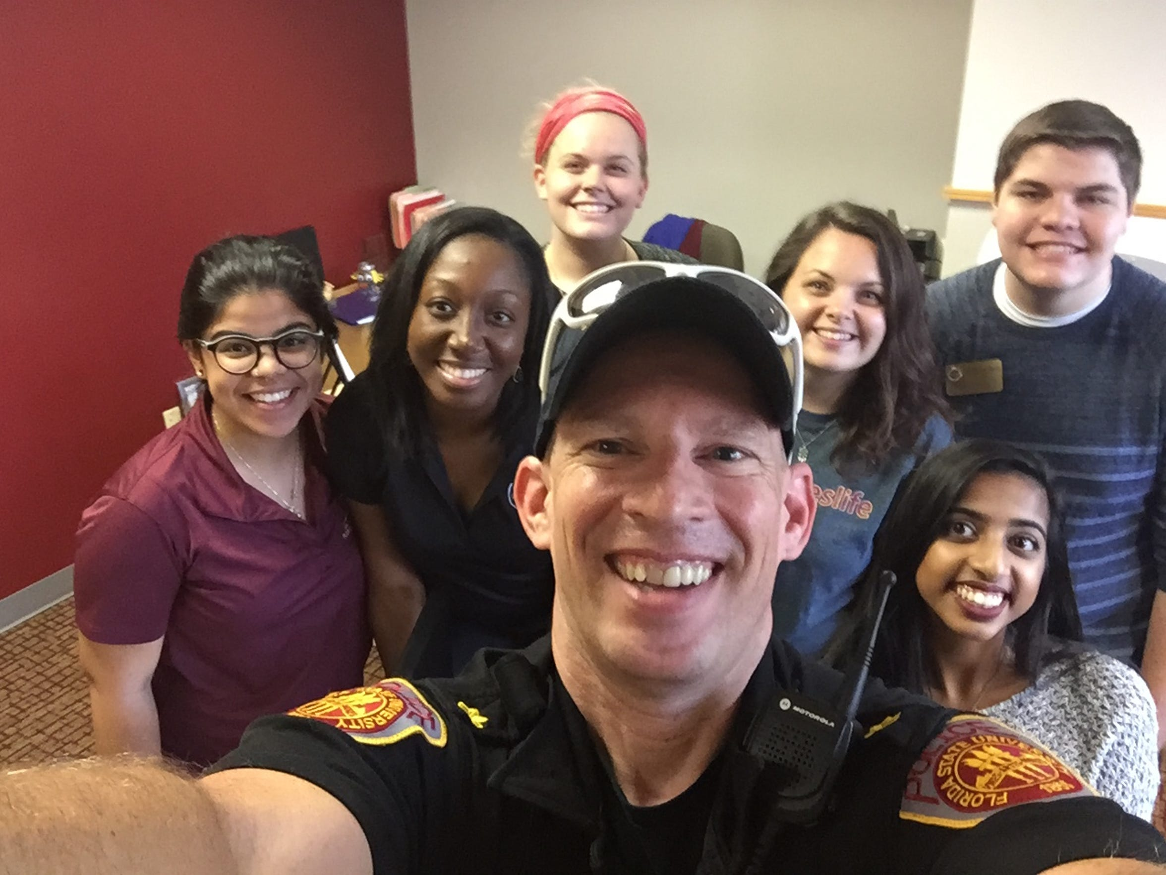 Major Russell poses for a picture with a mix of University Housing staff and students during residence hall move-in.