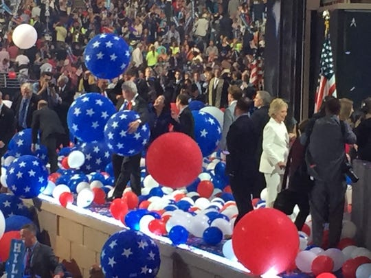Former President Bill Clinton, left, holds balloons while his wife Hillary gives an interview after accepting her nomination Thursday night.