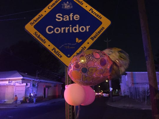 Balloons flutter from a Safe Corridor sign near the scene where an 8-year-old Camden girl was shot  by a stray bullet Wednesday. The corridors are intended to provide secure routes for students going to and from city schools.