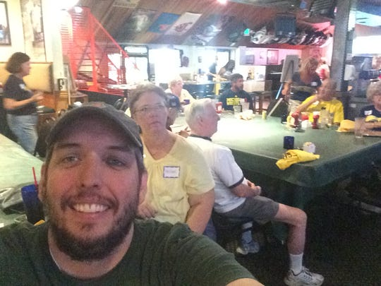Sports columnist Shad Powers, a Michigan State grad, takes a selfie with the University of Michigan spirit group assembled at The Beer Hunter in La Quinta.