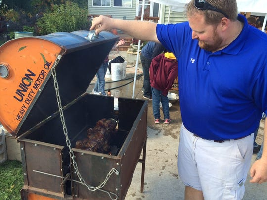 Tony Deich inspects chicken roasting in a grill his
