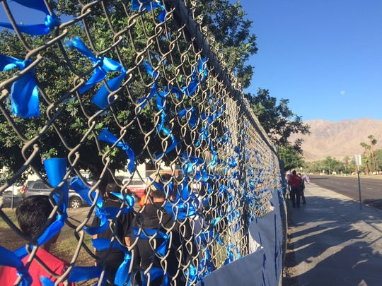 Blue ribbons decorate the fence at Raymond Cree Middle School on Vista Chino in Palm Springs on Tuesday morning as the school awaits the procession carrying the body of slain officer Lesley Zerebny to pass by.