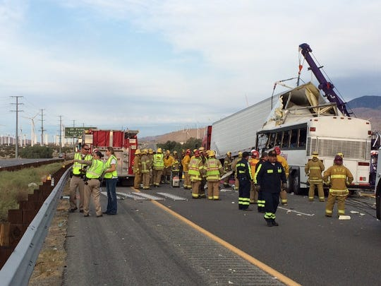 Emergency personnel work to remove victims from a tour bus crash that has killed at least 11 people in Palm Springs early Sunday. The crash occurred just after 5 a.m. along westbound Interstate 10. About 30 others have been hospitalized. A portion of I-10 has been shut down.