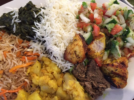 A plate full of Kabuly Palau, seasoned spinach stew, yellow seed rice, Afghan salad, chicken kabob, beef kabob and eggplant potato stew.