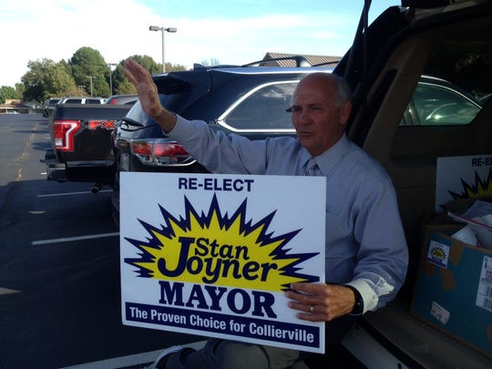 Collierville Mayor Stan Joyner waves to voters Monday from his perch on the back tailgate of his SUV outside Collierville Church of Christ, an early-voting site.