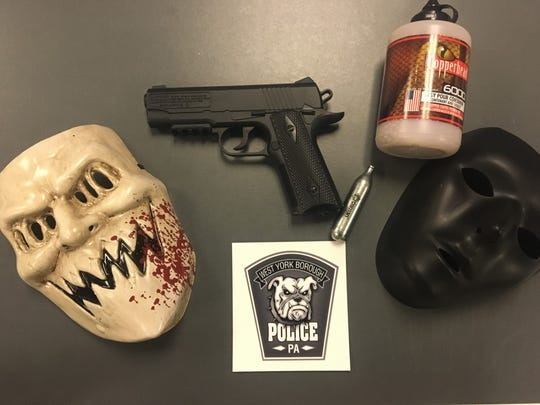 Police say they arrested a man and a juvenile on Monday night after they allegedly donned masks and pointed a BB gun at trick-or-treaters.