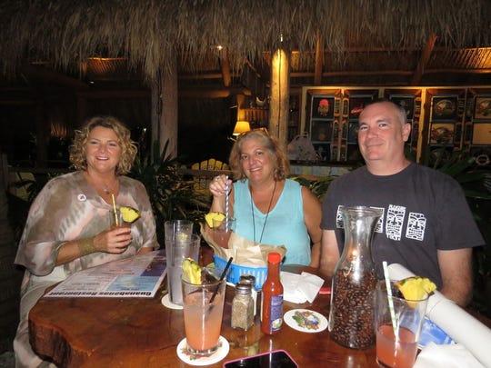 "Sue Barati Snyder, Lisa DiBlasio Hoyer and Glen Hoyer enjoy a signature drink ""Pink Dolphin Delight"" at the recent fundraiser held at Guanabanas restaurant in Jupiter."