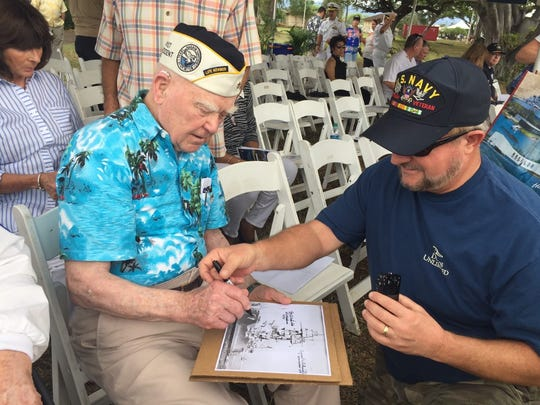 USS Oklahoma survivor Roy Carter of Washington state signs an autograph for a relative of another military member who survived the Pearl Harbor attack. Carter was one of three survivors of the ship to attend the 75th anniversary of the attack in Oahu, Hawaii.