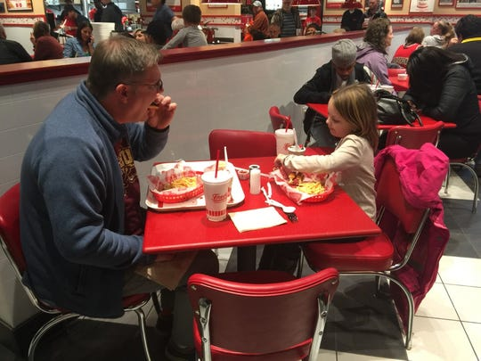 Freddy's restaurant customers Shane Feys and his daughter, Samantha Feys, 9, of Carmel, enjoyed a hamburger, a hot dog and some shoestring fries Monday, Dec. 12, 2016, during a training night at the new Westfield restaurant. Shane's son, Jason, works at the restaurant.
