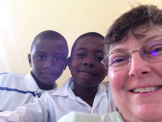 Kim Guard poses for a selfie with some Haitian children during one of her mission trips.
