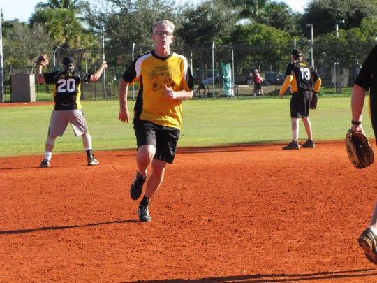 Mike Shone of the Brewery races into third base as Nick Jacullo (no. 20)  calls from the ball from the outfield.