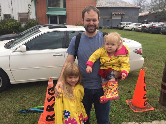 Chris Osmar, center, stands with his 6-year-old daughter Violet, left, and 2-year-old daughter Scout, right, before with Women's March on Tallahassee Saturday.