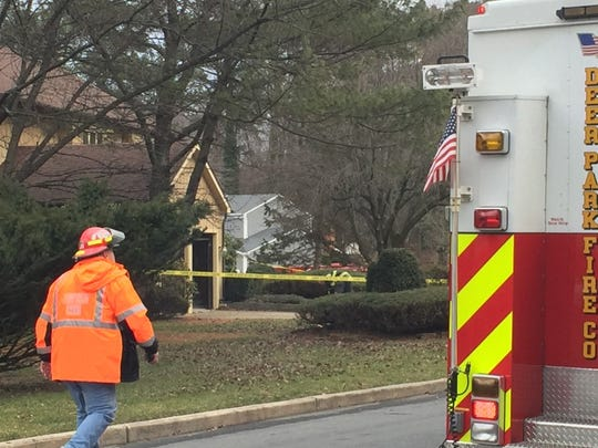 A firefighter walks toward police tape at the scene of a Cherry Hill house fire Tuesday.