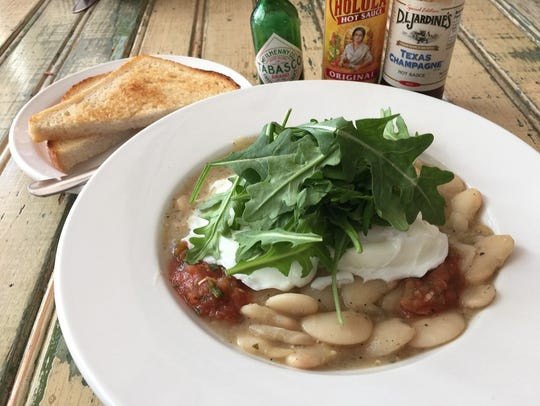 Poached eggs and arugula over butter bean stew.