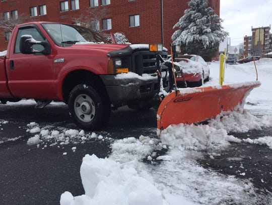 A snow plow clears the parking lot at Poplar Terrace,